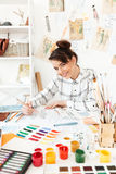Young happy lady fashion illustrator drawing. Picture of young happy lady fashion illustrator sitting at the table and drawing. Looking at camera stock image