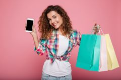 Young happy lady holding shopping bags and smartphone Stock Images
