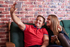 Young happy-looking couple is smiling lovely while taking selfie Royalty Free Stock Photography