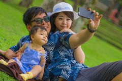 Young happy loving Asian Japanese family with parents and sweet baby daughter at city park together with father taking selfie pic. Young happy and loving Asian royalty free stock photo