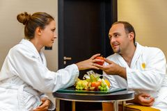 Young happy loving Caucasian couple of man and woman in white bathrobes talking after spa on honeymoon. Different fruits lying on royalty free stock photos