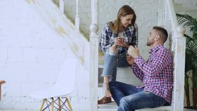 Young happy and loving couple drink tea and talking while sitting on stairs in living room at home. Young happy and loving couple drink tea and talking while stock images