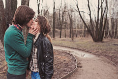 Young happy loving couple kissing on the walk in early spring. Day Royalty Free Stock Images
