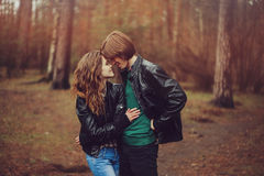 Young happy loving couple in leather jackets hugs outdoor on cozy walk in forest Stock Image