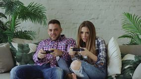 Young happy and loving couple play console game with gamepad and have fun sitting on couch in living room at home. Young happy and loving couple play console Stock Photo
