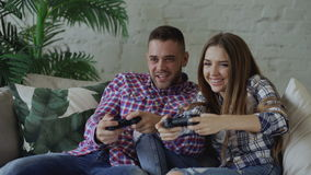Young happy and loving couple play console game with gamepad and have fun sitting on couch in living room at home stock footage
