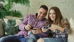 Young happy and loving couple play console game with gamepad and have fun sitting on couch in living room at home. Young happy and loving couple play console Royalty Free Stock Photography