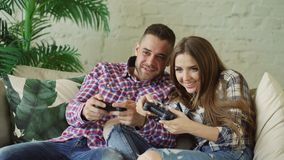 Young happy and loving couple play console game with gamepad and have fun sitting on couch in living room at home. Young happy and loving couple play console stock images