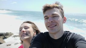 Young happy loving couple smiling into the camera in selfie mode on the rocky beach. Strong waves hitting the rocks. Young happy loving couple smiling into the stock video footage