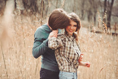 Young happy loving couple walking on country field, cozy mood Stock Photos