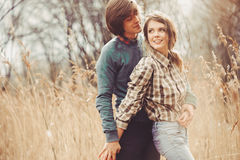 Young happy loving couple walking on country field, cozy mood Royalty Free Stock Photography