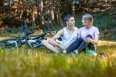 Young Happy Loving Couple. Walking in the park on bicycles. Comm. Unication Royalty Free Stock Images