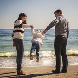 Young happy loving family with small kid in the middle, having fun at beach together near the ocean, holding arms, happy lifestyle Royalty Free Stock Images