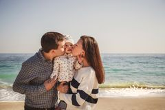 Young happy loving family with small kid in the middle, kissing each other near the ocean at the beach, happy lifestyle family con Royalty Free Stock Photography