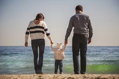Young happy loving family with small kid in the middle, walking at beach together near the ocean, holding arms, happy lifestyle fa Royalty Free Stock Photography