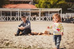 Young happy loving father with small daughter enjoying time at beach, father is looking after daughter, happy lifestyle family con Royalty Free Stock Photography