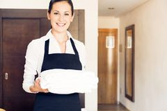 Maid Making A Hotel Room. Young happy maid cleaning uo a hotel room Stock Photo