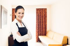Maid Making A Hotel Room. Young happy maid cleaning up a hotel room Royalty Free Stock Photo