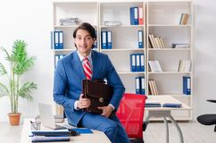 The young happy male employee in the office. Young happy male employee in the office stock photo