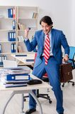 The young happy male employee in the office. Young happy male employee in the office stock photography