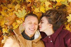 Young and happy. Young male and female lying down on yellow maple leaves smiling happy having good time eyes closed Stock Photography
