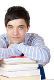 Young happy male student leaning on study books. Young happy male student is smiling and leaning on his study books. Isolated on white Royalty Free Stock Photos