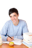 Young happy male student learning from study books. Young student is sitting on desk with study books and learns for his exams. He smiles happy into camera Stock Photos