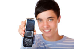 Young happy male teenager shows mobile phone Royalty Free Stock Photography