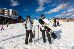 Young happy males in ski suits standing with snowboards and skis royalty free stock photo