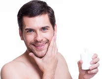 Young happy man applying cream. Stock Images