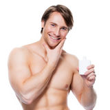 Young happy man applying lotion on face. Stock Photos