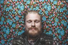 Young Happy Man With Beard Lie On Colorful Background. Creativity Concept. Young Happy Man With Beard Lie On Colorful Flower Background. Creativity Concept Stock Photography