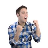 Young happy man in blue shirt cheering. Studio Shot Royalty Free Stock Photography