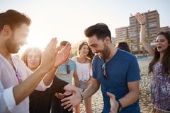 Young happy man dancing on beach with friends royalty free stock photos