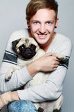 Young happy man with dog. Pug Stock Photo
