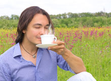 Young happy man drinking coffee outdoors Stock Photography