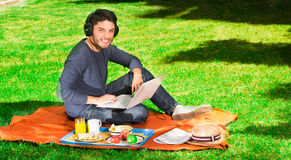 Young happy man enjoying picnic in park while he uses his computer wearing a headphones Stock Photography