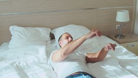 Young, happy man falling on bed in room, slow motion stock video