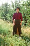 Man garden collect ripe apples hat green red proprietor worker owner harvest. Young happy man in the garden collect ripe apples stock photography
