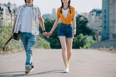 Young and happy man with guitar walking and holding hand of girl stock images
