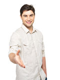 Young happy man with handshake gesture in casuals Royalty Free Stock Images
