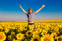 Young happy man have fun on the field with sunflowers at sunset. Stock Image