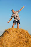 Young happy man on haystack Stock Image