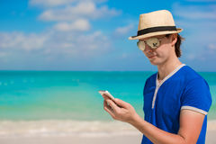 Young happy man with his phone on beach vacation Stock Photography