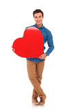Young happy man holding a big heart. Full body picture of a young happy man holding a big heart on white background Royalty Free Stock Image