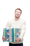 Young happy man holding big heavy gift. Young casual caucasian man holding big heavy christmas gift and happy smiling looking at camera stock images