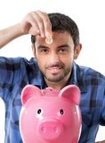 Young happy man holding coin putting it into pink piggy bank Royalty Free Stock Image