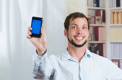 Young happy man holding his cell phone and showing Royalty Free Stock Photos