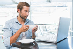 Young happy man holding his coffee while looking at his laptop Royalty Free Stock Image