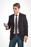 Young happy man holding mobile phone. Portrait of handsome young business man using cell phone, smiling Royalty Free Stock Photos